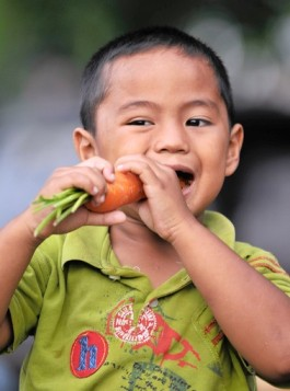A young boy eats a carrot at a collapsed